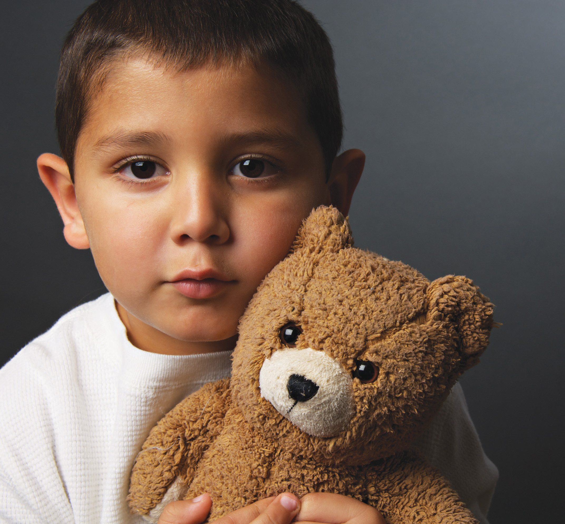 This picture is a sad boy holding his teddy bear.